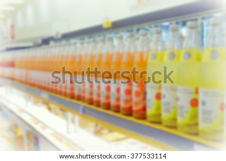 Blurred juice bottles at a supermarket - stock photo