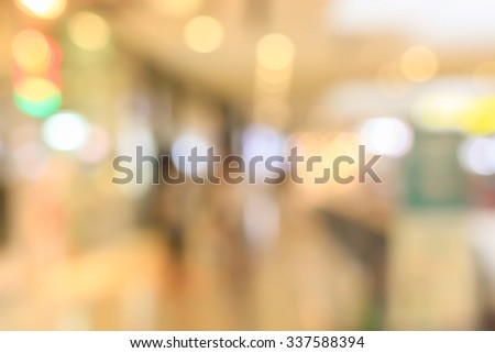 blurred light in warm cream tone backgrounds:blur of department store shopping concept: out of focus concept.blur of motion bokeh circle light christmas festive backdrop conception.  - stock photo