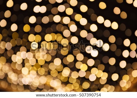 Blurred lights as Christmas background. Golden color on black