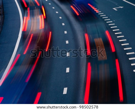 blurred lights of cars on a highway at evening - stock photo