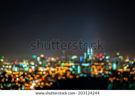 Blurred lights of Kuala Lumpur skyline, love shape bokeh - stock photo