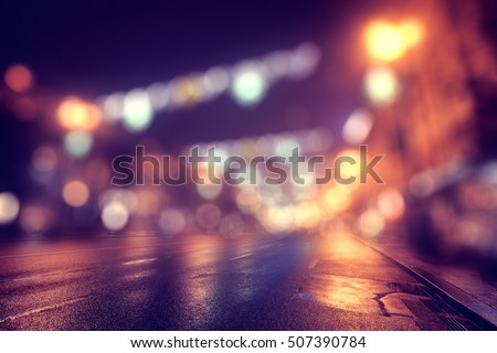 Blurred lights of night city at christmas time. Wet asphalt on foreground