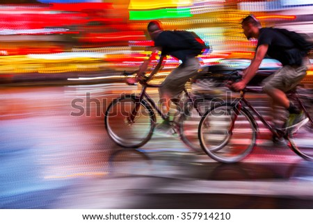 blurred lights on a night urban scene and cyclists silhouettes - stock photo