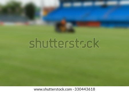 Blurred man mowing the grass on a football stadium. - stock photo