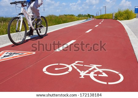 Blurred man riding bicycle on a bike path  - stock photo