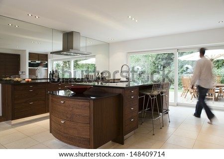 Blurred man walking in modern and spacious kitchen with dining area in the porch - stock photo
