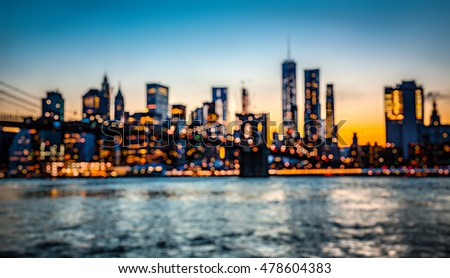 Blurred Manhattan skyline with Brooklyn Bridge at night
