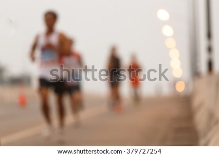 Blurred marathon runners on the road. - stock photo