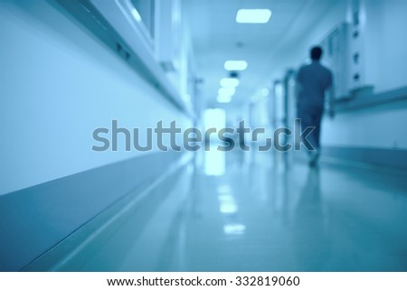 Blurred medical background. Moving human figure in the hospital corridor