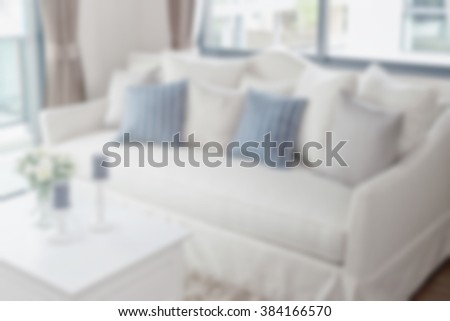 blurred modern living room with row of pillows on sofa for background - stock photo