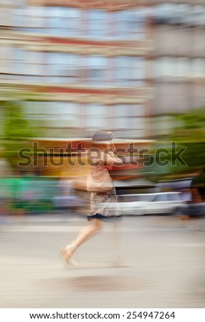 Blurred motion image of a woman walking down a city street - stock photo
