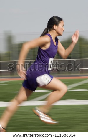 Blurred motion of Asian female athlete running on racetrack - stock photo