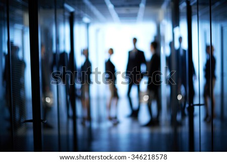 Blurred motion of business team standing at office - stock photo