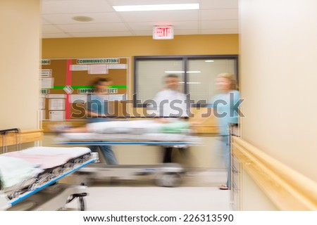 Blurred motion of doctor and nurses with stretcher in hospital corridor - stock photo