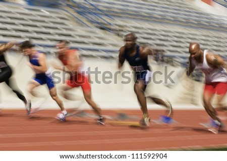 Blurred motion of male athletes racing in stadium - stock photo