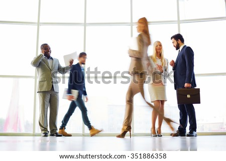 Blurred motion of several people working at office - stock photo