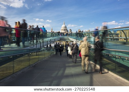 Blurred motion view over the Millennium footbridge looking towards St. Paul's Cathedral - stock photo