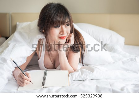 blurred motion young sexy asian woman on white bed, Pretty lady enjoying spare time in her bed.