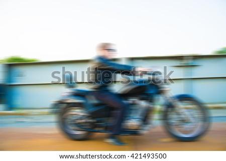 blurred motorcyclist against yellow sunset Man wearing black leather jacket sunglasses jeans Idea of freedom in speed Biker drive on metal bridge chopper motor bike Empty copy space for inscription - stock photo