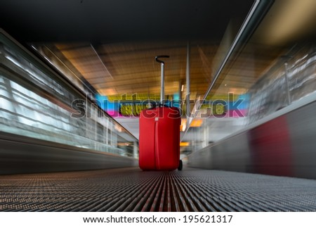 blurred moving escalator with red trolley in airport