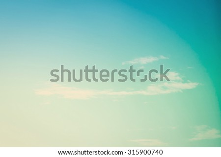 Blurred nature background of minimal blue cyan sky with soft clouds under wind movement in vintage style: Blurry natural clouds under slow wind in summer holiday vacation day in minimalism style    - stock photo