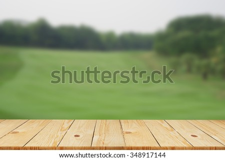 blurred nature in sunny day backgrounds with old vintage wooden desk tabletop:blurry of natural outdoor backdrop with wood perspective floorboard:put and show your products on display or wallpaper - stock photo