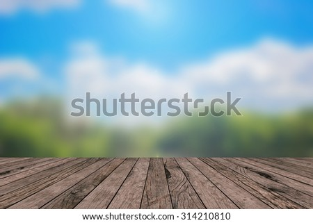 Blurred nature park outdoors backgrounds vintage with wooden desk table or wooden paving:blurred of nature park  with shiny sunlight in a day.put  show promotion products on display montage screen - stock photo