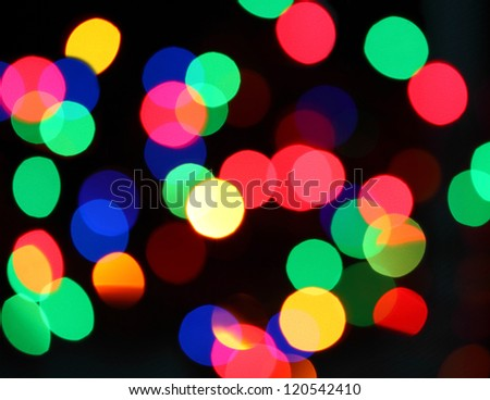 Blurred neon disco light dots pattern on dark background
