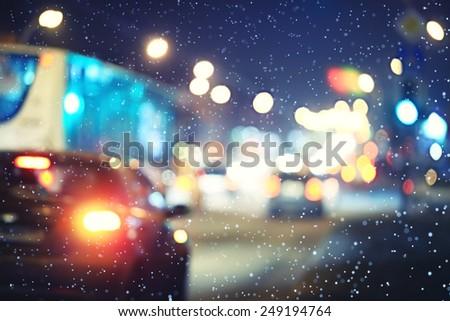 blurred night background city traffic road city lights winter snow glare - stock photo