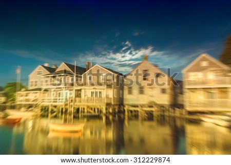 Blurred night view of wooden homes over water, Nantucket. - stock photo