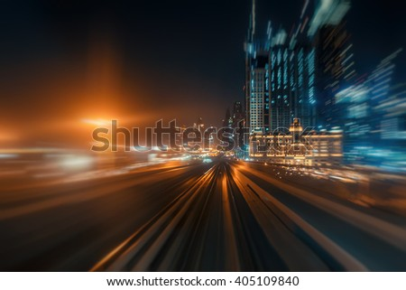 Blurred nighttime skyline with illuminated architecture of Dubai. View from a metro car. - stock photo