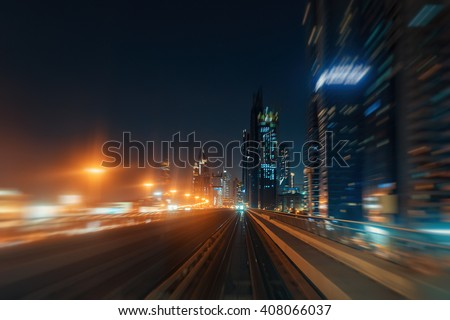 Blurred nighttime skyline with illuminated architecture of Dubai. View from a metro car. Travel background.