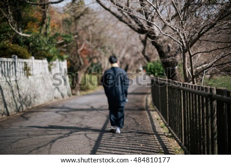 Blurred of a Japanese man with traditional clothing on street ,leaf in Autumn-vintage style