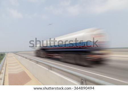 blurred of big fuel truck goes on highway  asphalt road - stock photo