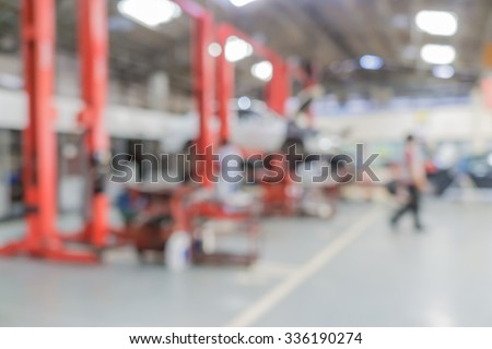 Blurred of car technician repairing the car in garage background, Interior of a car repair station. - stock photo