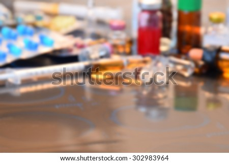 Blurred of Glass Medicine Vials medicine pill and capsule Syringe on x-ray film over doctor table for background (shallow DOF) - stock photo