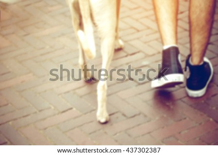 blurred of man walking with dog in city street,vintage warm light tone.