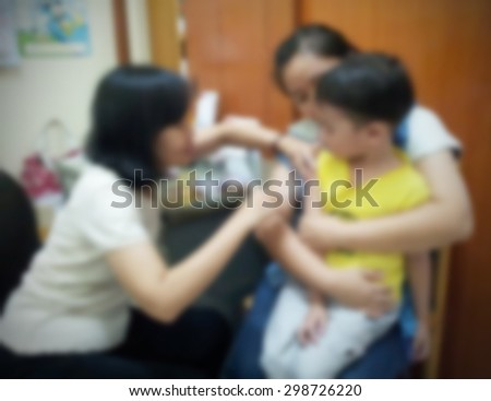 Blurred of mother comforting son having injection