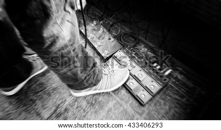 Blurred of musician pushing a guitar pedal on black and white tone