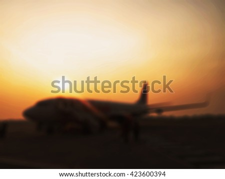 Blurred of passenger and commercial airplane against sunrise background. - stock photo