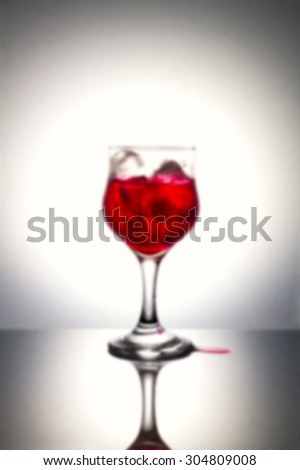 Blurred of red syrup on ice with gray background.Used color tool for color tone and blurry tool.