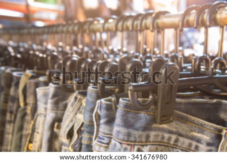 Blurred of row of hanged blue jeans in a shop