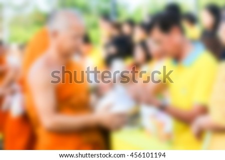 blurred people give food and drink for alms to Buddhist monks in to celebrate 70 years King Rama IX of Thailand taking to the Thorne  - stock photo