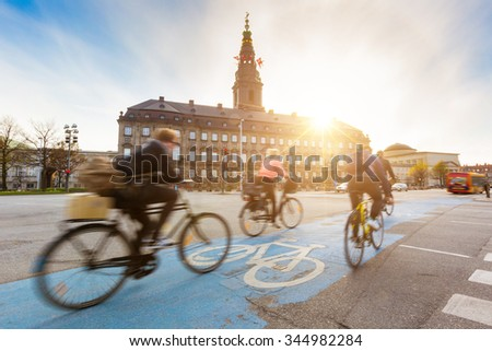 Blurred people going by bike in Copenhagen, with Christiansborg palace on background. Many persons prefer biking instead of taking car or bus to move around the city. Urban lifestyle concept.