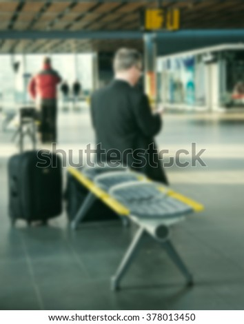 Blurred people inside in train station or airport, with luggage and bags.Travel and urban lifestyle concepts. - stock photo