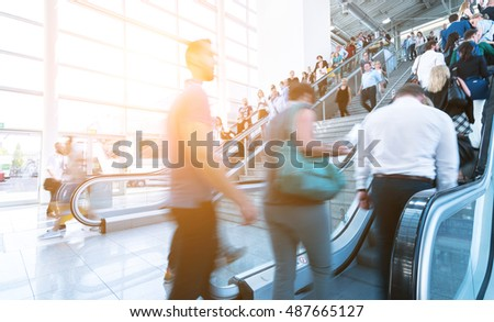 Blurred people on a fair using a skywalk/staircase
