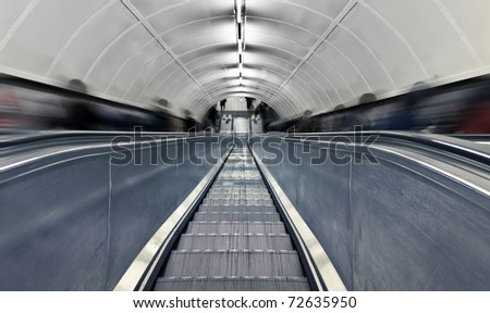 Blurred people on escalator. London subway station at rush hour. - stock photo