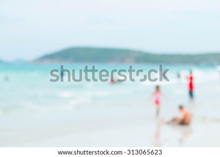 Blurred people on white sand beach with blue sea an sky background