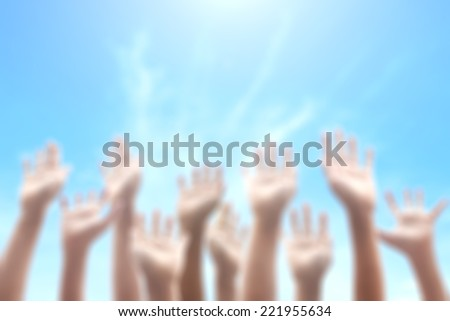 Blurred people raising hands on blue sky background. International Volunteer Day, Human Rights Day, International Human Solidarity Day, Praise and Worship, Christian, Trustconcept. - stock photo