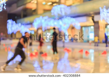 Blurred people skating on the ice rink that decoration with light bulbs. - stock photo